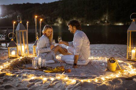Pareja con una cena romántica, abrazos y tintineo de copas de vino en el lugar bellamente decorado iluminado con diferentes luces de la playa al atardecer