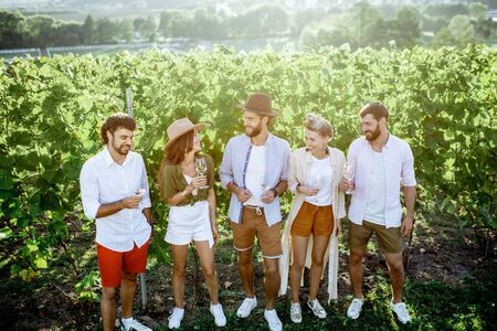 Group of young friends dressed casually hanging out together, tasting wine on the vineyard on a sunny summer morning