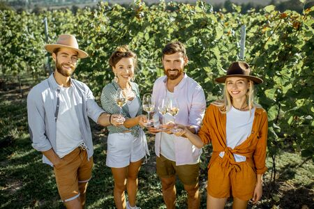 Portrait of a young sylish friends standing with wine glasses, hanging out together on the vineyard on a sunny summer morning