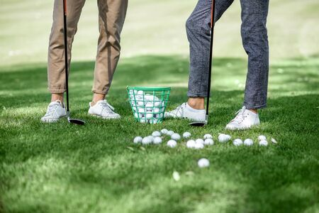 Friends standing together with golf equipment and balls on the green grass, cropped image with no face Stockfoto