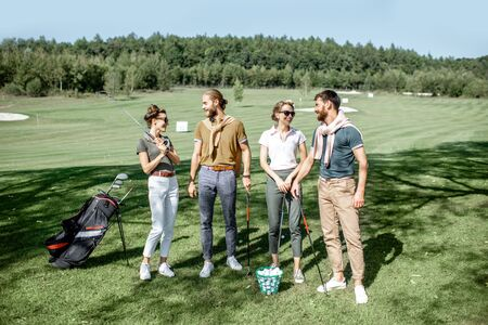 Young and elegant friends standing together with golf equipment, having fun during a golf play on the beautiful course on a sunny day