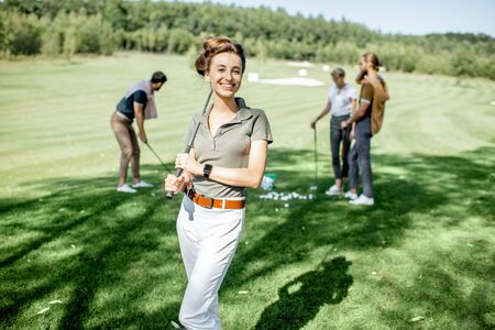 Portrait of an elegant young woman standing with golf putter and friends playing golf on the background 版權商用圖片