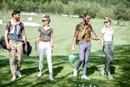 Young and elegant friends walking with golf equipment, hanging out together before the golf play on the beautiful course on a sunny day Stockfoto