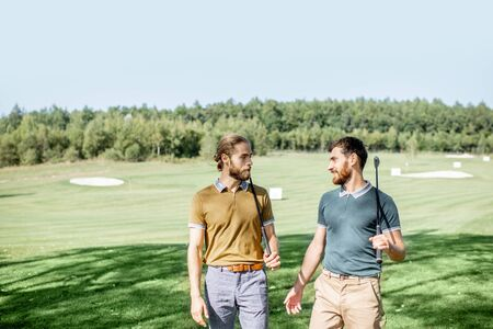 Two male best friends walking with golf equipment on beautiful playing course, talking and having fun during a game on a sunny day 版權商用圖片