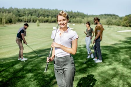Portrait of an elegant young woman standing with golf putter and friends playing golf on the background Stockfoto