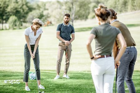 Group of a young people dressed casually playing golf on the beautiful golf course on a sunny day, woman swinging a putter