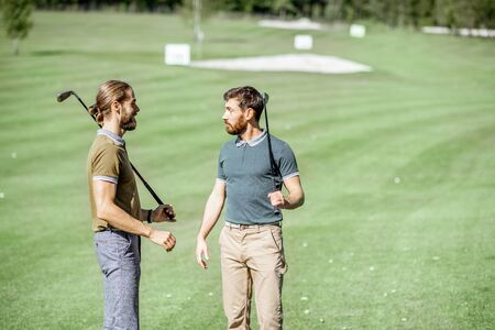 Two male best friends standing with playing equipment on a golf course, hanging out together during a game on a sunny day