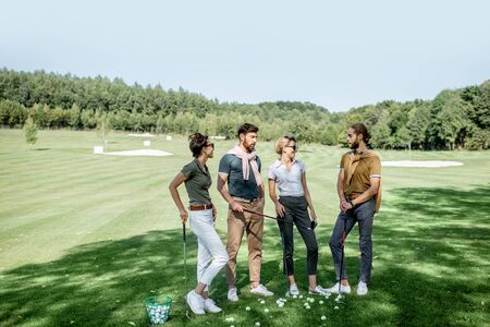 Young and elegant friends standing together with golf equipment during a golf play on the beautiful course on a sunny day