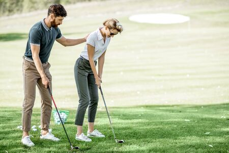 Male instructor teaching young woman to play golf on the golf course on a sunny day