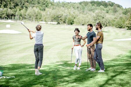 Gruppe junger Leute, die an einem sonnigen Tag lässig gekleidet auf dem schönen Golfplatz Golf spielen?