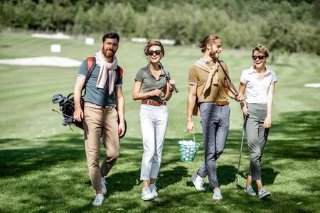 Young and elegant friends walking with golf equipment, hanging out together before the golf play on the beautiful course on a sunny day 版權商用圖片