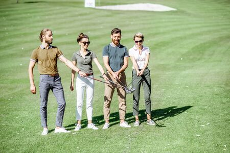 Portrait of a young group of friends keeping golf putters together as a team players on the golf course outdoors