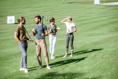 Group of friends talking and walking with putters during the golf play on the beautiful course on a sunny day