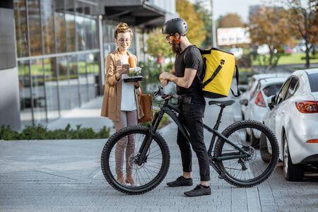 Kurier, der einer jungen Geschäftsfrau auf einem Fahrrad mit Thermorucksack frische Mittagessen liefert. Konzept für die Lieferung von Speisen zum Mitnehmen im Restaurant Standard-Bild