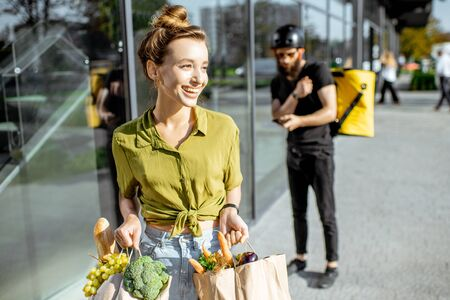 Young and happy woman carrying bags full of fresh food received from a delivery man. Courier standing with delivery bag on the background Stockfoto