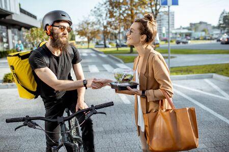 Mensajero entregando almuerzos frescos a una joven mujer de negocios en bicicleta con mochila térmica. Concepto de entrega de comida de restaurante para llevar Foto de archivo