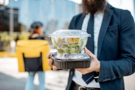 Zakenman met lunchdozen met afhaalmaaltijden ontvangen van een koerier buitenshuis. Bezorgconcept voor eten
