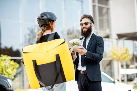 Young female courier delivering takeaway lunches with a thermal bag to an office worker dressed in the suit near the office building outdoors