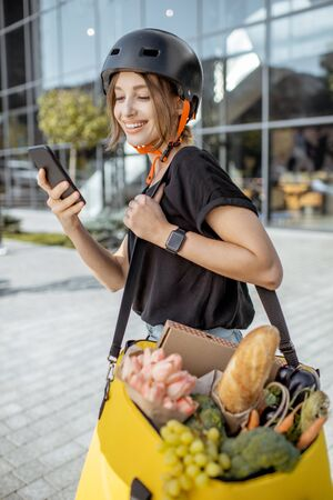 Young female courier delivering fresh food, standing with smartphone and backpack full of products outdoors
