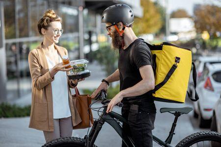 Kurier, der einer jungen Geschäftsfrau auf einem Fahrrad mit Thermorucksack frische Mittagessen liefert. Konzept für die Lieferung von Speisen zum Mitnehmen im Restaurant