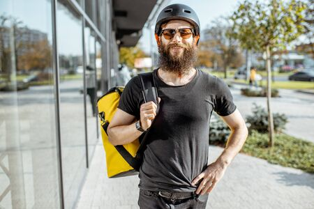 Portrait of a young bearded courier in protective helmet standing with yellow thermal bag for food delivering on the street outdoors