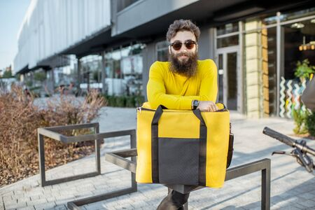 Portrait of a young bearded man as a deliveryman standing with yellow thermal bag for food delivery on the city street near the office building