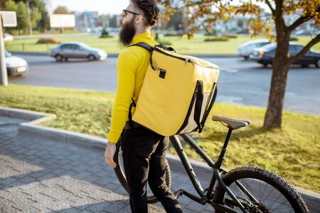Young courier delivering food in yellow thermo bag, walking with bicycle in the city. Delivery service concept Reklamní fotografie