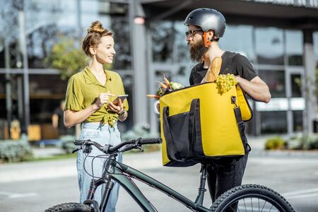 Male courier on a bicycle delivering fresh food using thermal bag to a young happy woman outdoors. Groceries delivery concept