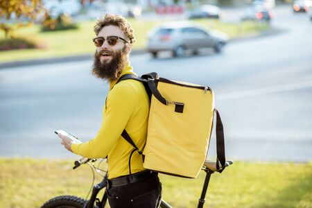 Young courier delivering food on a bicycle, checking order with a smart phone while standing on the street in the city. Delivery service concept