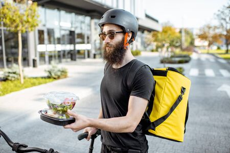 Young and cheerful courier waiting for a client with takeaway lunches near the building outdoors, delivering restaurant food on a bicycle using thermal bag