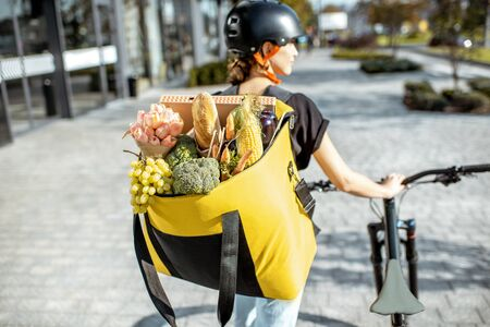 Female courier carrying backpack full of fresh products, delivering groceries and flowers. Fresh products delivery concept Reklamní fotografie
