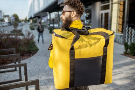 Delivery Man standing with yellow thermo backpack for food delivery with empty space to copy paste on the street outdoors