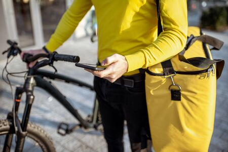 Man delivering food with thermo bag and bicycle, checking an order with smart phone, close-up view Reklamní fotografie