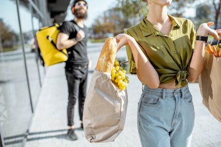 Woman carrying paper bags full of fresh food received from a courier. Close-up view focused on products with delivery man on the background
