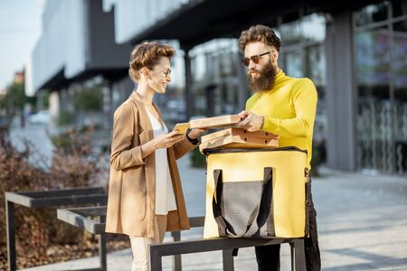 Male courier delivering pizza with thermal bag to a young businesswoman, standing together near the office building. Delivery service concept