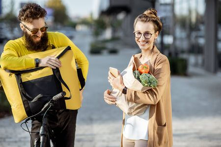 Male courier on a bicycle delivering fresh food using thermal bag to a young business woman outdoors. Groceries delivery concept