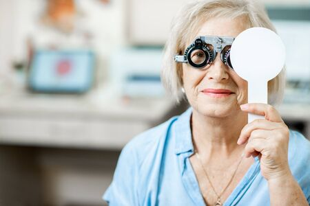 Senior woman checking vision with eye test glasses and scapula during a medical examination at the ophthalmological office Stock Photo
