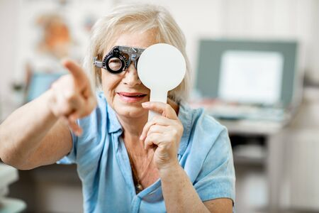 Senior woman with poor eyesight checking vision squinting her face during a medical examination at the ophthalmological office Imagens