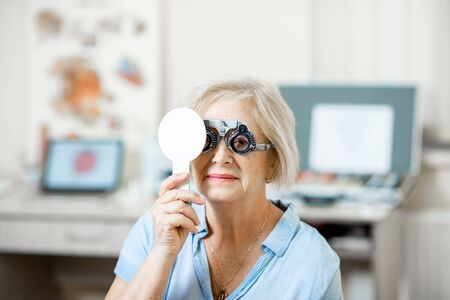 Senior woman checking vision with eye test glasses and scapula during a medical examination at the ophthalmological office Imagens