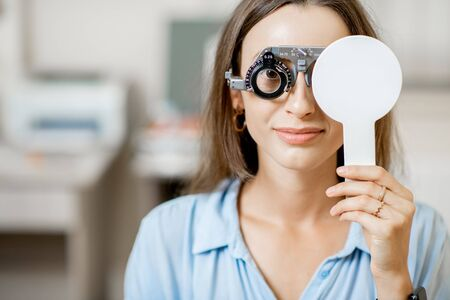 Young woman checking vision with eye test glasses during a medical examination at the ophthalmological office Foto de archivo