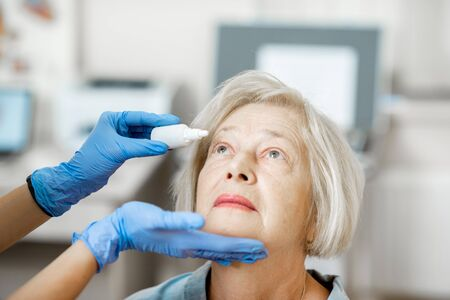 Doctor dripping eye drops on eyes of a senior patient during a treatment at the ophthalmological office 版權商用圖片