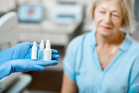 Nurse in medical gloves holding white bottles or droppers with eye medicine with senior patient on the background, close-up