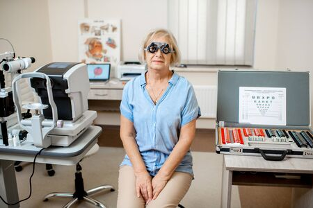 Portrait of a senior woman checking vision with eye test glasses during a medical examination at the ophthalmological office