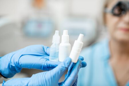Nurse in medical gloves holding white bottles or droppers with eye medicine with senior patient on the background, close-up view, bottles with blank space