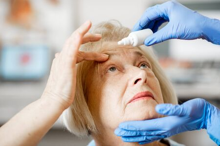 Doctor or nurse in medical gloves dripping eye drops on eyes of a senior patient during a treatment at the ophthalmological office, close-up view 版權商用圖片 - 133386523