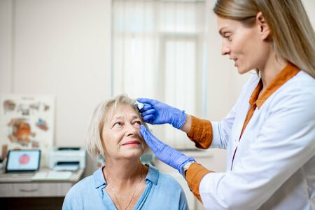 Female doctor dripping eye drops on eyes of a senior patient during a treatment at the ophthalmological office