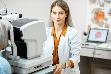 Portrait of a female ophthalmologist examining eyes of a senior patient using digital microscope during a medical examination in the office