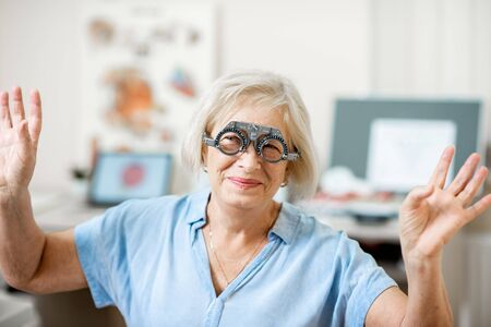 Senior woman checking vision with eye test glasses during a medical examination at the ophthalmological office