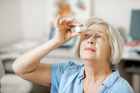 Senior woman dripping some medicine with dropper on her eyes at the ophthalmological office. Concept of eye treatment with eye drops