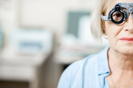 Close-up of a senior woman checking vision with eye test glasses during a medical examination at the ophthalmological office Imagens
